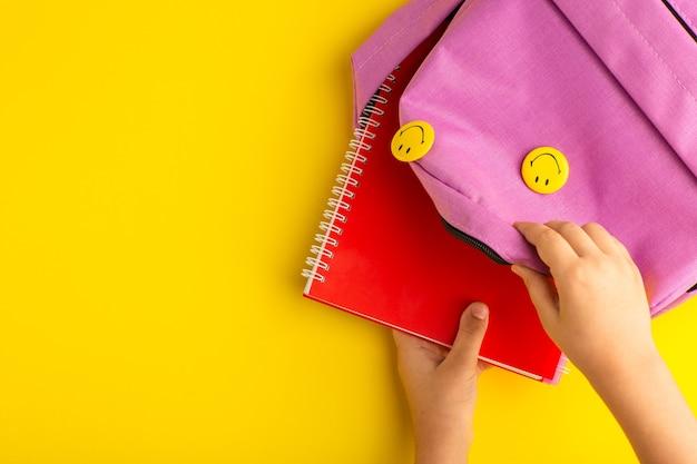 Draufsicht kleines kind, das für schule vorbereitet, das heft aus tasche auf gelber oberfläche nimmt