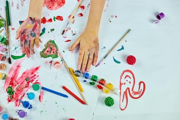Draufsicht kleines mädchen mit gemalten bunten aquarellhänden, kind, das am tisch sitzt und zeichnet, konzept der kunstschule, mädchenkindmalerei zu hause