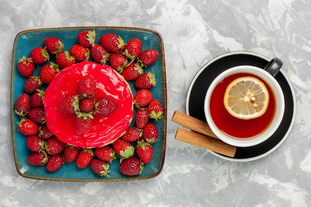 Draufsicht köstlich aussehender kuchen kleiner kuchen mit tasse tee und frischen erdbeeren auf hellweißem oberflächenkuchen-keks-kekscreme-zuckersüß