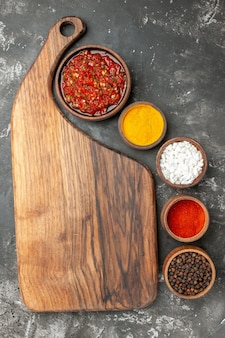 Draufsicht köstliche adjika in einer schüssel hölzernen servierbrett mit griff verschiedene gewürze in kleinen schlägen auf grauem hintergrund