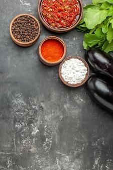 Draufsicht köstliche adjika verschiedene gewürze in kleinen auberginengrüns auf grauem hintergrund