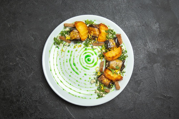 Draufsicht köstliche auberginenröllchen mit ofenkartoffeln im teller auf dem dunklen hintergrundgericht mahlzeit abendessen rollkartoffelgemüse