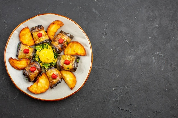 Draufsicht köstliche auberginenrollen gekochtes gericht mit ofenkartoffeln auf dem dunklen hintergrund