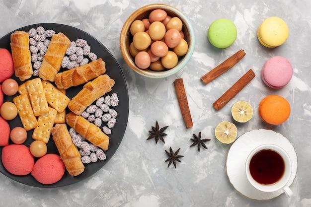 Draufsicht köstliche bagels mit crackern zimt und macarons auf dem weißen schreibtischkuchenkeks süßer zuckerkuchenplätzchen knusprig