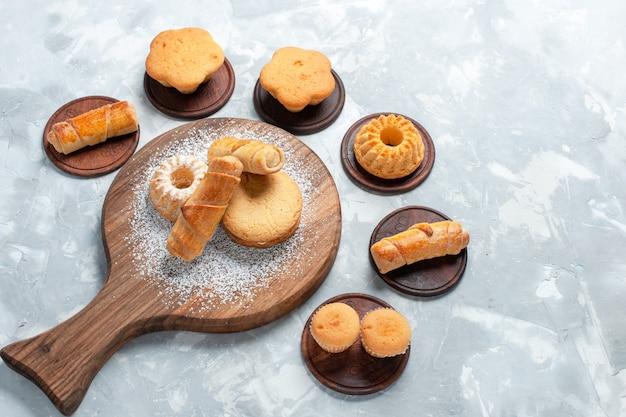 Draufsicht köstliche bagels mit kleinen kuchen und keksen auf hellweißem hintergrund.