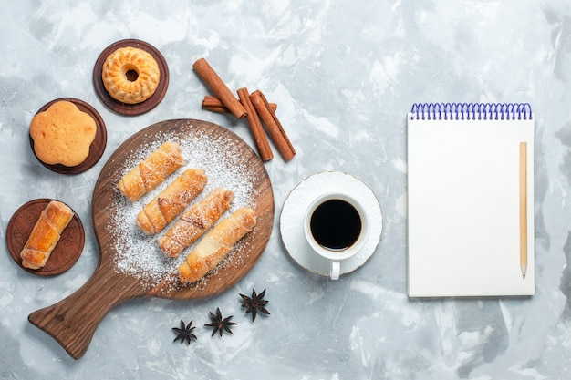 Draufsicht köstliche bagels mit tasse tee und zimt auf hellweißem hintergrund.