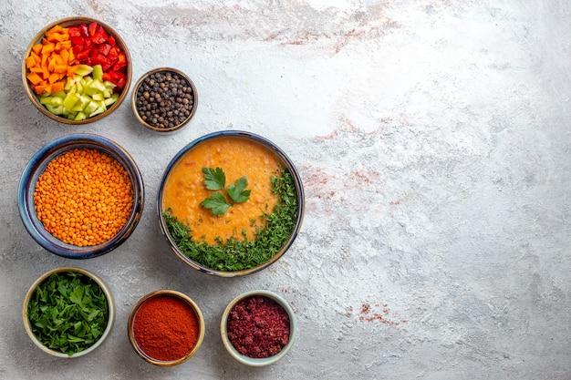 Draufsicht köstliche bohnensuppe mit grüns und gewürzen auf hellweißem hintergrundmahlzeit-nahrungsmittelsuppengemüse
