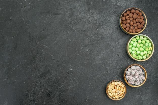 Draufsicht köstliche bonbons kleine zuckerwaren für tee auf dunklem raum