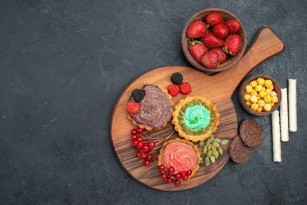 Draufsicht köstliche cremige kuchen mit früchten auf dunklem tisch süßer keksplätzchen