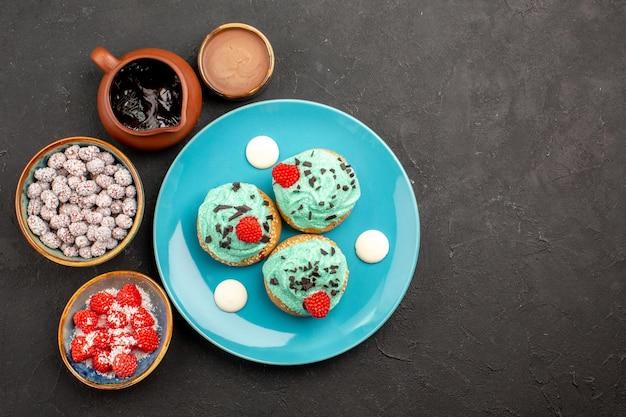 Draufsicht köstliche cremige kuchen mit süßigkeiten auf dunklem hintergrund dessertkuchen keks süßigkeiten keksfarbe