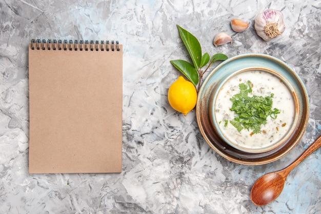 Draufsicht köstliche dovga-joghurtsuppe mit grüns auf weißem boden milchsuppengericht molkerei
