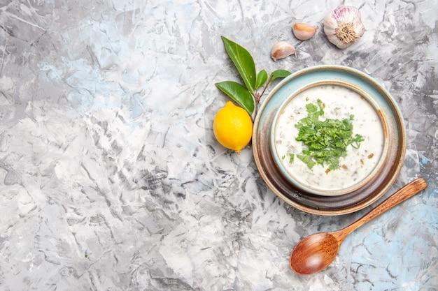 Draufsicht köstliche dovga-joghurtsuppe mit grüns auf weißem tisch milchsuppengericht molkerei