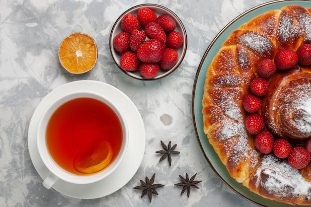 Draufsicht köstliche erdbeerkuchen mit tasse tee auf der weißen oberfläche kuchenkuchen keks süßer zucker tee backen