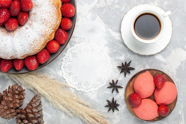 Draufsicht köstliche erdbeerkuchen mit tasse tee auf weiß