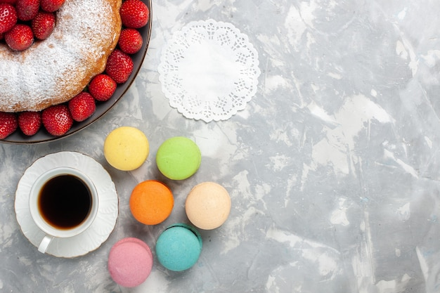 Draufsicht köstliche erdbeerkuchen mit tasse tee macarons auf weiß