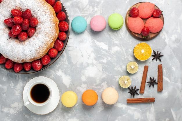 Draufsicht köstliche erdbeerkuchen mit tee und früchten auf weiß