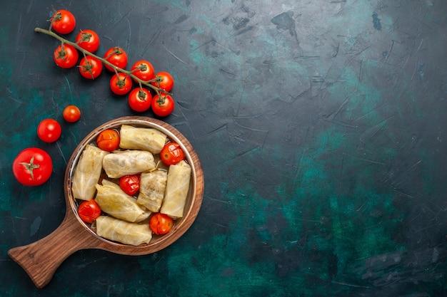 Draufsicht köstliche fleischmahlzeit, die in kohl mit frischen tomaten auf dunkelblauem schreibtischfleischnahrungsmittelabendessen kaloriengemüsegeschirr gekocht wird
