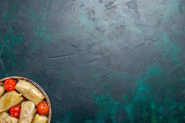 Draufsicht köstliche fleischmahlzeit, die in kohl mit tomaten auf dem dunkelblauen schreibtischfleischnahrungsmittelabendessen kaloriengemüses kochen gerollt wird