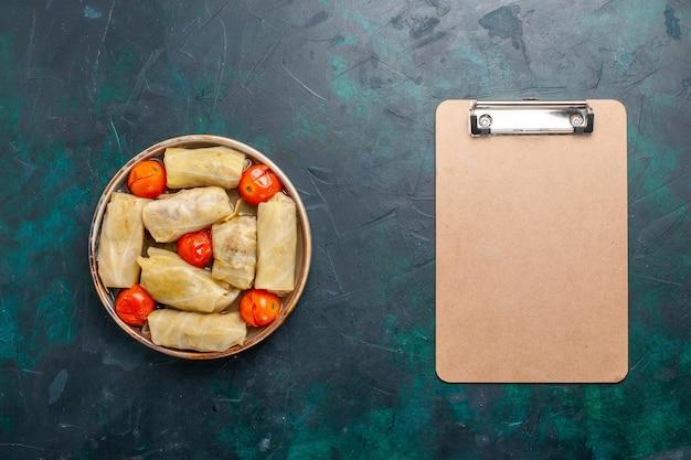 Draufsicht köstliche fleischmahlzeit, die in kohl mit tomaten und notizblock auf dem dunkelblauen schreibtischfleischnahrungsmittelabendessen kaloriengemüse gekocht wird