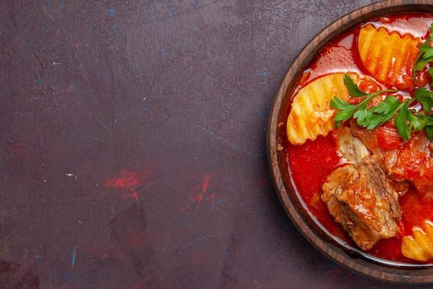 Draufsicht köstliche fleischsoßensuppe mit grüns und in scheiben geschnittenen kartoffeln auf dunkler oberflächensoßen-suppe-mahlzeit-abendessen-gericht