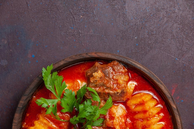 Draufsicht köstliche fleischsoßensuppe mit grüns und in scheiben geschnittenen kartoffeln auf dunkler schreibtischsoßensuppe mahlzeit essen abendessen