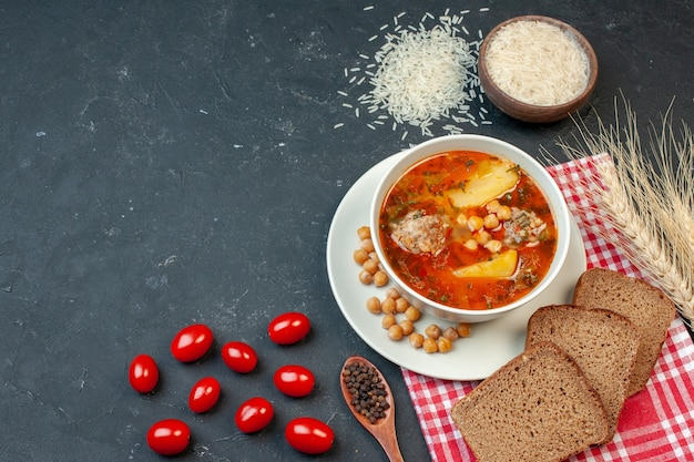 Draufsicht köstliche fleischsuppe mit brot und tomaten auf dunklem hintergrund