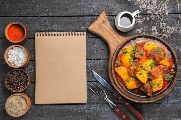 Draufsicht köstliche fleischsuppe mit gemüse und kartoffeln auf dunklem boden