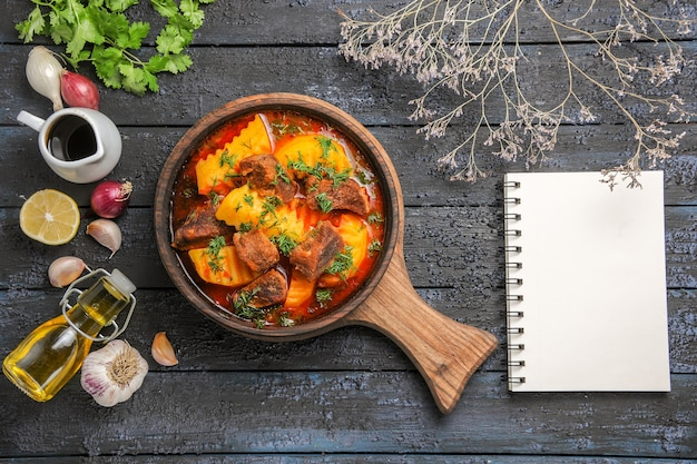 Draufsicht köstliche fleischsuppe mit kartoffeln und gemüse auf dem dunklen schreibtisch