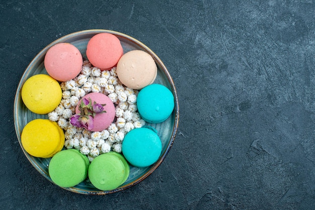 Draufsicht köstliche französische macarons mit bonbons im tablett auf dem dunklen raum