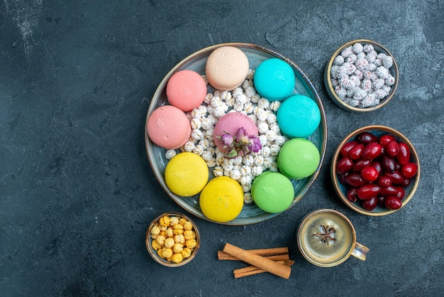 Draufsicht köstliche französische macarons mit bonbons und hartriegel auf dunklem raum