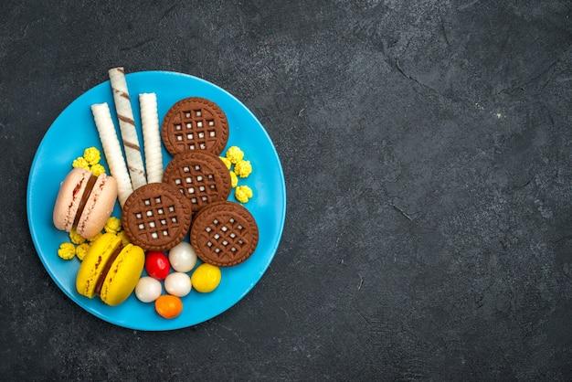 Draufsicht köstliche französische macarons mit bonbons und schokoladenkeksen auf dunkelgrauem hintergrundkekszuckerkuchen süßer backkeks
