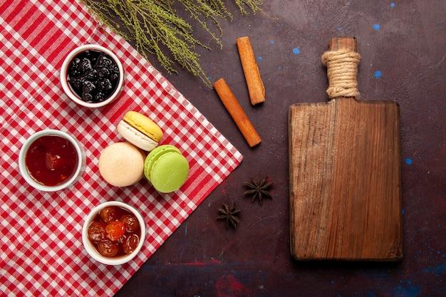 Draufsicht köstliche französische macarons mit fruchtmarmeladen auf süßem fruchtmarmeladenkuchen-keks süßem zucker des dunklen hintergrunds