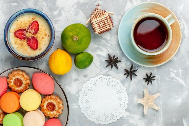Draufsicht köstliche französische macarons mit keksen dessert und tee auf hellweißem hintergrund backen kuchen keks zucker süßes foto