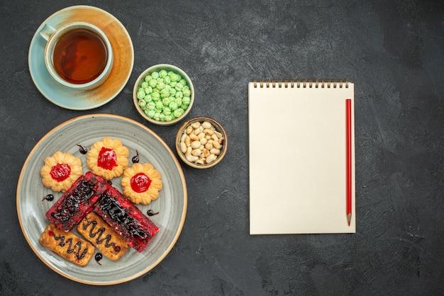 Draufsicht köstliche fruchtige kuchen mit keksen und tasse tee auf dem dunklen hintergrund zuckerkekskuchen keks süßer teekuchen