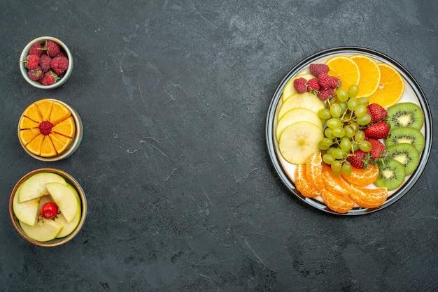 Draufsicht köstliche fruchtzusammensetzung frisch geschnittene und ausgereifte früchte auf dunklem hintergrund reife frische gesundheitsdiätfrucht ausgereift