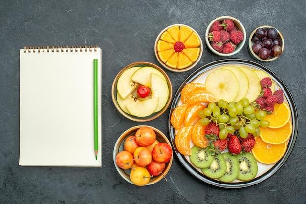 Draufsicht köstliche fruchtzusammensetzung frische und geschnittene früchte auf dem dunklen hintergrund reife frische gesundheitsfrucht weich