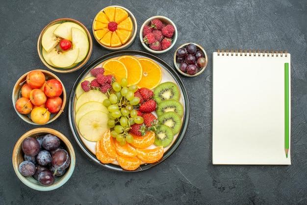 Draufsicht köstliche fruchtzusammensetzung frische und geschnittene früchte auf dunklem hintergrund reife frische gesundheitsdiätfrüchte mellow