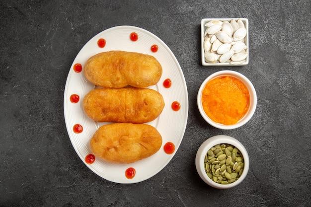 Draufsicht köstliche gebackene heiße kuchen mit samen auf grauer oberfläche ofen backen kuchenkuchenkartoffel