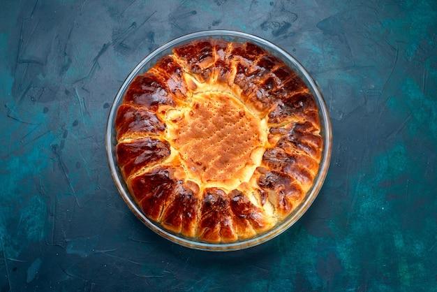 Draufsicht köstliche gebackene kuchenrunde geformte süße innere glaspfanne auf dem hellblauen hintergrund.