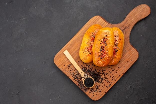 Draufsicht köstliche gebackene pastetchen frisch aus dem ofen auf dem dunklen hintergrund kuchengebäck backen teig ofen fleischkuchen