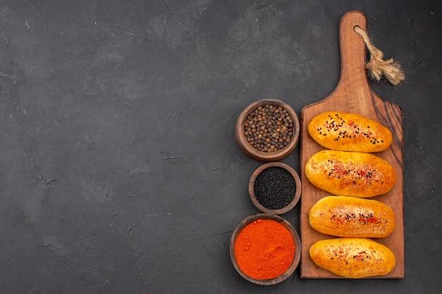 Draufsicht köstliche gebackene pastetchen frisch aus dem ofen mit gewürzen auf dunklem hintergrund kuchengebäck backen teig ofen fleischkuchen