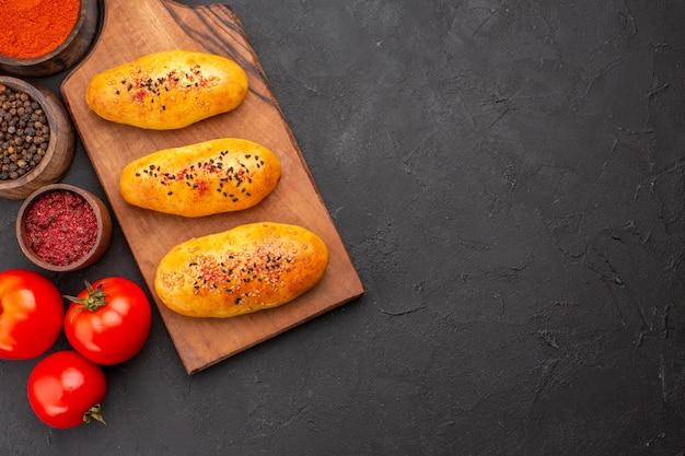 Draufsicht köstliche gebackene pastetchen frisch aus dem ofen mit gewürzen auf grauem schreibtischkuchenofen gebäckteigfleischkuchen backen