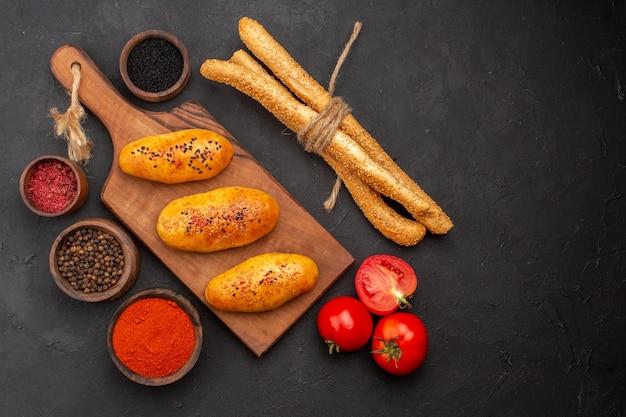 Draufsicht köstliche gebackene pastetchen mit gewürzen und brötchen auf grauer oberfläche fleischpastete gebäckkuchen-backofen