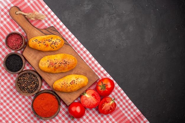 Draufsicht köstliche gebackene pastetchen mit verschiedenen gewürzen auf dem dunklen hintergrundgebäck backen teig ofenkuchen-fleischkuchen