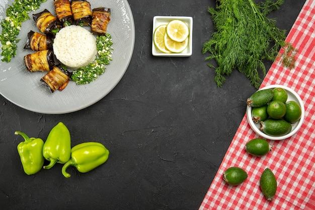 Draufsicht köstliche gekochte auberginen mit reis feijoa und zitronenscheiben auf dunkler oberfläche abendessen essen kochen reismehl