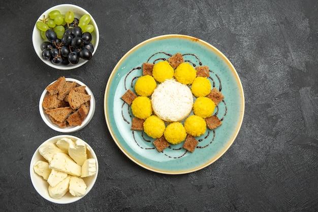 Draufsicht köstliche gelbe bonbons mit kuchentrauben und käse auf dem dunklen hintergrund zuckerfruchtsüßigkeitenteekuchen süß