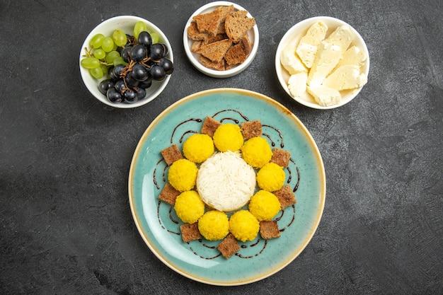 Draufsicht köstliche gelbe bonbons mit kuchentrauben und käse auf dunklem schreibtisch zuckerfruchtsüßigkeiten teekuchen süß