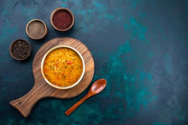 Draufsicht köstliche gemüsesuppe in rundem teller mit gewürzen auf dem dunkelblauen schreibtisch.