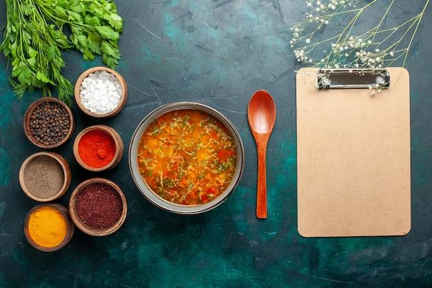 Draufsicht köstliche gemüsesuppe mit gewürzen auf einer grünen oberfläche lebensmittelgemüse zutaten suppe produkt mahlzeit