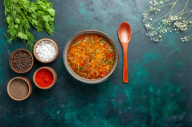 Draufsicht köstliche gemüsesuppe mit gewürzen auf grünem hintergrund lebensmittelgemüse zutaten suppenprodukt mahlzeit